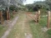 Hardhouten slagboom over toegangsweg naar een bungalow in het duingebied