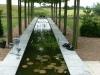 Verhoogde waterspiegel voor serre woning onder plataan loofgang met uitzicht op de polder